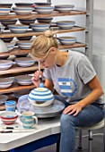 ALHAM FARM, SOMERSET: CORNISHWARE: THE POTTERY - VICKY APPLYING ICONIC BLUE STRIPE BY HAND TO FIRED BOWLS