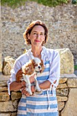 ALHAM FARM, SOMERSET: CORNISHWARE: KARINA RICKARDS IN POTTERY YARD HOLDING PET DOG ROSIE, A CAVALIER KING CHARLES SPANIEL