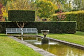 RADCOT HOUSE, OXFORDSHIRE: THE LONG POND. POOL, RILL, WATER, YEW HEDGES, HEDGING, WHITE, METAL, SEATING, BENCH, CLIPPED, TOPIARY