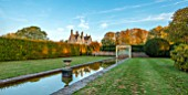 RADCOT HOUSE, OXFORDSHIRE: THE HOUSE SEEN FROM THE LONG POND. BEECH HEDGES, HEDGING, POOL, CANAL, GAZEBO, SEAT, SEATING, AUTUMN, REFLECTIONS, REFLECTED