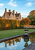 RADCOT HOUSE, OXFORDSHIRE: THE HOUSE SEEN FROM THE LONG POND. BEECH HEDGES, HEDGING, POOL, CANAL, AUTUMN, REFLECTIONS, REFLECTED