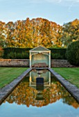 RADCOT HOUSE, OXFORDSHIRE: THE LONG POND. BEECH HEDGES, HEDGING, POOL, CANAL, GAZEBO, SEAT, SEATING, AUTUMN, REFLECTIONS, REFLECTED