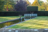 RADCOT HOUSE, OXFORDSHIRE: THE LONG POND. YEW HEDGES, HEDGING, POOL, CANAL, AUTUMN, REFLECTIONS, REFLECTED, STONE, URN, WHITE METAL SEAT, SEATING