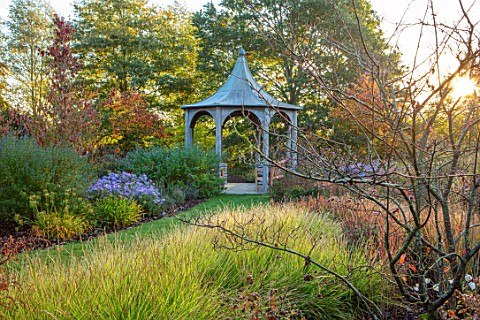 RADCOT_HOUSE_OXFORDSHIRE_GRASS_PATH_TO_PAVILION_WITH_SESLERIA_AUTUMNALIS_AND_ASTER_X_FRIKARTII_MONCH