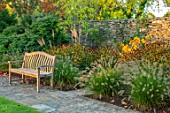 RADCOT HOUSE, OXFORDSHIRE: WOODEN BENCH BESIDE LAWN, HAMAMELIS, PENNISETUM, AUTUMN, BORDERS, FALL, LATE SUMMER, WALLS