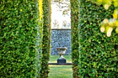 RADCOT HOUSE, OXFORDSHIRE: VIEW THROUGH BEECH HEDGES, HEDGING TO STONE URN, CONTAINER IN LONG POND