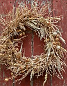 FLOWERS FROM THE FARM, MARBURY HALL, DESIGNER SOFIE PATON-SMITH: DRIED SEED HEAD WREATH ON SHED DOOR. NIGELLA, PENNY CRESS, POPPY HEADS, NATURAL, WREATHS