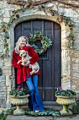PYTTS HOUSE, OXFORDSHIRE: CHRISTMAS, BACK DOOR, WREATH, ANNA DE KEYSER HOLDING ONE OF HER PET DOGS