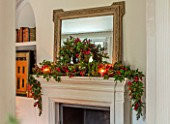 GIBBONS CROFT, WEST CLANDON, SURREY: CHRISTMAS - SITTING ROOM, STONE MANTELPIECE, MIRROR, CANDLES, WREATH