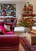 GIBBONS CROFT, WEST CLANDON, SURREY: CHRISTMAS - SITTING ROOM, RED SOFAS, PAINTING BY FAMILY FRIEND, CHRISTMAS TREE
