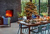 GIBBONS CROFT, WEST CLANDON, SURREY: CHRISTMAS. OPEN PLAN KITCHEN, DINING ROOM. GLASS WALLED EXTENSION, SLATE WALL, FIREPLACE, WOODEN DINING TABLE, CHAIRS, CHRISTMAS TREE