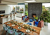 SPRINGFIELDS HOUSE, WEST CLANDON, SURREY: OPEN PLAN KITCHEN, DINING ROOM. SLATE WALL, FIREPLACE, KITCHEN ISLAND UNIT, TABLE, CHAIRS, CHRISTMAS TREE