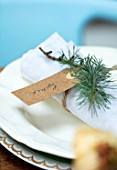 GIBBONS CROFT, WEST CLANDON, SURREY: CHRISTMAS PLACE SETTING ON TABLE. LINEN NAPKIN, FIR SPRIG AND CARDBOARD LUGGAGE LABEL NAME TAG