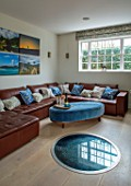 SPRINGFIELDS HOUSE, WEST CLANDON, SURREY: OPEN PLAN LIVING AREA. FAMILY SEATING AREA. LARGE LEATHER SOFA, CUSHIONS, PHOTOGRAPHS, GLASS COVERED WELL SET IN LIMESTONE FLOOR