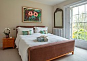 GIBBONS CROFT, WEST CLANDON, SURREY: MASTER BEDROOM: BED, WHITE BEDDING, CUSHIONS, MIRROR, MODERN ART