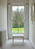 SPRINGFIELDS HOUSE, WEST CLANDON, SURREY: UPPER HALL, VIEW ONTO GARDEN, SASH WINDOW, WHITE LEATHER AND CHROME FOOT STOOL