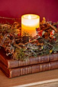 THE CONIFERS, OXFORDSHIRE: CHRISTMAS - LIVING ROOM, ANTIQUE BOOKS WITH CANDLE