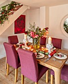 THE CONIFERS, OXFORDSHIRE: CHRISTMAS - KITCHEN DINING ROOM - TABLE, CHAIRS, MIRROR, PRINT OF RED CAMELLIA BY CLIVE NICHOLS, STAIRCASE, VASE WITH AMARYLLIS, PINEAPPLE CANDLES