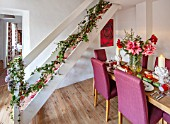 THE CONIFERS, OXFORDSHIRE: CHRISTMAS - KITCHEN DINING ROOM - TABLE, CHAIRS, PRINT OF RED CAMELLIA BY CLIVE NICHOLS, STAIRCASE, VASE WITH AMARYLLIS, PINEAPPLE CANDLES