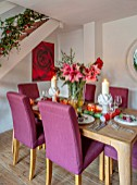 THE CONIFERS, OXFORDSHIRE: CHRISTMAS - KITCHEN DINING ROOM - TABLE, CHAIRS, MIRROR, PRINT OF RED CAMELLIA BY CLIVE NICHOLS, STAIRCASE, VASE WITH AMARYLLIS, PINEAPPLE CANDLESS