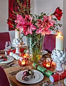 THE CONIFERS, OXFORDSHIRE: CHRISTMAS - KITCHEN DINING ROOM - TABLE, CHAIRS, PRINT OF RED CAMELLIA BY CLIVE NICHOLS, VASE WITH AMARYLLIS, PINEAPPLE CANDLES, CRACKERS
