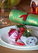 THE CONIFERS, OXFORDSHIRE: CHRISTMAS - KITCHEN DINING ROOM - TABLE, PLATE WITH NAPKIN, IVY AND ANTIQUE BAUBLE DECORATION, CRACKER, CANDLE