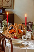 MARBURY HALL, SHROPSHIRE: DESIGNER SOFIE PATON-SMITH - TAPESTRY DINING ROOM, SWEDISH CHRISTMAS - CHRISTMAS TREE, FRESH FRUITS IN HAND MADE STRAW BASKET, CANDLES