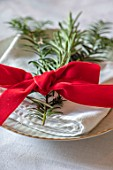 MARBURY HALL, SHROPSHIRE: DESIGNER SOFIE PATON-SMITH - TAPESTRY DINING ROOM, SWEDISH CHRISTMAS - NAPKIN DECORATION OF ROSEMARY AND RED FELT RIBBON