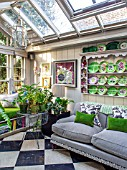 BUTTER WAKEFIELD HOUSE, LONDON: CHRISTMAS - THE GARDEN ROOM. GLASS CONSERVATORY JUST OFF THE KITCHEN WITH SOFA AND BUTTERS CHINA PLATES DISPLAYED ON PLATE RACK. FERNS