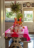 BUTTER WAKEFIELD HOUSE, LONDON: CHRISTMAS - KITCHEN - TABLE, PINK TABLECLOTH, CANDLES, TULIPS, ANEMONES, RANUNCULUS