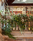 WARDINGTON MANOR, OXFORDSHIRE: FLORIST SHANE CONNOLLY - LIVING ROOM, HALLWAY - STAIRS AND BALCONY WITH NATURAL CHRISTMAS DECORATIONS - BRACKEN, HONESTY, MISTLETOE, IVY, LICHEN