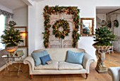 MERRYWOOD, JACKY HOBBS HOUSE, LONDON: SITTING ROOM, VINTAGE FRENCH DOORS, SOFA, CUSHIONS, CHRISTMAS TREES, VINTAGE STONE URN, VINTAGE FRENCH MIRROR