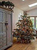 MERRYWOOD, JACKY HOBBS HOUSE, LONDON: SITTING ROOM - FRENCH VINTAGE CUPBOARD, WOODEN SLEIGH, CHRISTMAS TREE, DECORATIONS
