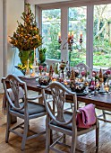 MERRYWOOD, JACKY HOBBS HOUSE, LONDON: SITTING ROOM - DINING AREA, WOODEN DINING TABLE AND CHAIRS, MIRRORS, CANDLES, METAL CROWNS, CHRISTMAS TREE