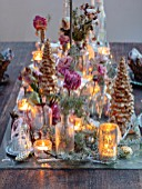 MERRYWOOD, JACKY HOBBS HOUSE, LONDON: SITTING ROOM - DINING AREA, WOODEN DINING TABLE, CANDLES, METAL CROWNS, CHRISTMAS TREE, PLACE SETTINGS, METAL GOBLETS, DRIED PEONY AND ROSES