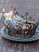 MERRYWOOD, JACKY HOBBS HOUSE, LONDON: WOODEN DINING TABLE, PLACE SETTING, METAL CROWN ON BEADED GLASS AND PEWTER PLATE, CUTLERY, GOBLET, LINEN NAPKIN, DRIED ROSE HEAD