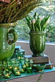 MERRYWOOD, JACKY HOBBS HOUSE, LONDON: DINING AREA, GREEN GLAZED CONTAINER WITH WHITE TULIPS, CHRISTMAS TREE, GREEN GLASS TEALIGHTS, VINTAGE BOOKS