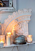 MERRYWOOD, JACKY HOBBS HOUSE, LONDON: DINING ROOM - VINTAGE FRENCH METAL GARDEN TABLE, VINTAGE PLASTER ARTEFACTS, WHITE CANDLES, METAL DECORATIVE DOME