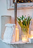 MERRYWOOD, JACKY HOBBS HOUSE, LONDON: DINING ROOM - VINTAGE FRENCH METAL GARDEN TABLE, VINTAGE PLASTER ARTEFACTS, WHITE CANDLES, WHITE TULIPS IN VASE