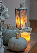JACKY HOBBS HOUSE, LONDON: SITTING ROOM. GREY VINTAGE FRENCH METAL GARDEN TABLE, METAL CANDLE LANTERN, DECORATIVE GREY PUMPKINS