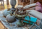 MERRYWOOD, JACKY HOBBS HOUSE, LONDON: DINING ROOM - CHRISTMAS DECORATION. GREY PUMPKINS, METAL VERDIGRIS URN, CONTAINER WITH BIRDS NEST, QUAILS EGGS, PHEASANT FEATHERS