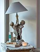 MERRYWOOD, JACKY HOBBS HOUSE, LONDON: DINING ROOM - CHRISTMAS, STONE CHERUB LAMP, GREY LINEN SHADE, BOOKS,CANDLE