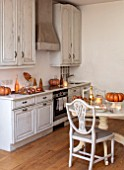 MERRYWOOD, JACKY HOBBS HOUSE, LONDON: WHITE KITCHEN, CHRISTMAS: ORANGE PUMPKINS, TABLE AND CHAIRS
