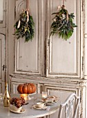 MERRYWOOD, JACKY HOBBS HOUSE, LONDON: WHITE KITCHEN, CHRISTMAS: ORANGE PUMPKINS, TABLE AND CHAIRS, VINTAGE FRENCH CUPBOARDS, PINE AND HYDRANGEA HANGING BOUQUETS