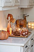 MERRYWOOD, JACKY HOBBS HOUSE, LONDON: WHITE KITCHEN, CHRISTMAS: ORANGE PUMPKINS, CANDLES, TRAY, BRONZE AND GOLD DECORATIONS, CHAMPAGNE, GLASES
