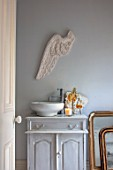 JACKY HOBBS HOUSE, LONDON: BATHROOM IN GREY. GREY VINTAGE WOODEN WASHSTAND, CERAMIC BOWL, CARVED PLASTER ANGELS WING ON WALL. CANDLE