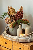MERRYWOOD, JACKY HOBBS HOUSE, LONDON: DISPLAY OF NATURAL DRIED HYDRANGEAS IN VINTAGE FRENCH COMPOTE JAR, STONE WARE BOTTLES, CANDLE, WICKER TRAY
