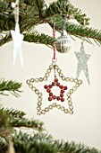 MERRYWOOD, JACKY HOBBS HOUSE, LONDON: DETAIL OF DIAMANTE STAR CHRISTMAS TREE DECORATION ON CHRISTMAS TREE WITH METAL STARS