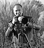 BLACK AND WHITE PHOTOGRAPH OF CLIVE NICHOLS WITH CAMERA