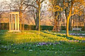 MORTON HALL, WORCESTERSHIRE: WHITE AND PURPLE CROCUS IN THE PARKLAND MEADOW. CROCUSES, CROCI, FEBRUARY, MEADOWS, NATURALISED, MASSES, BENCHES, SEATS, MONOPTEROS